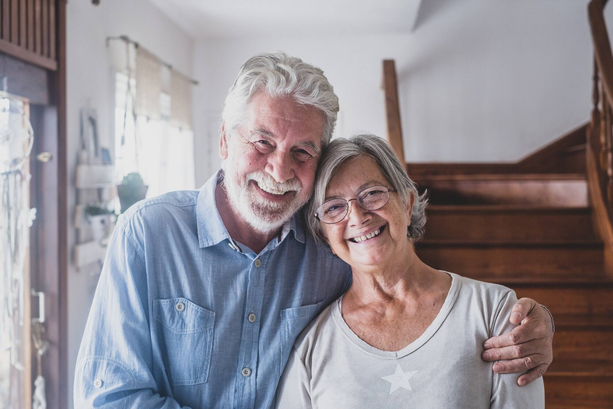Portrait of happy couple old people seniors hug together, looking at the camera, loving to mature